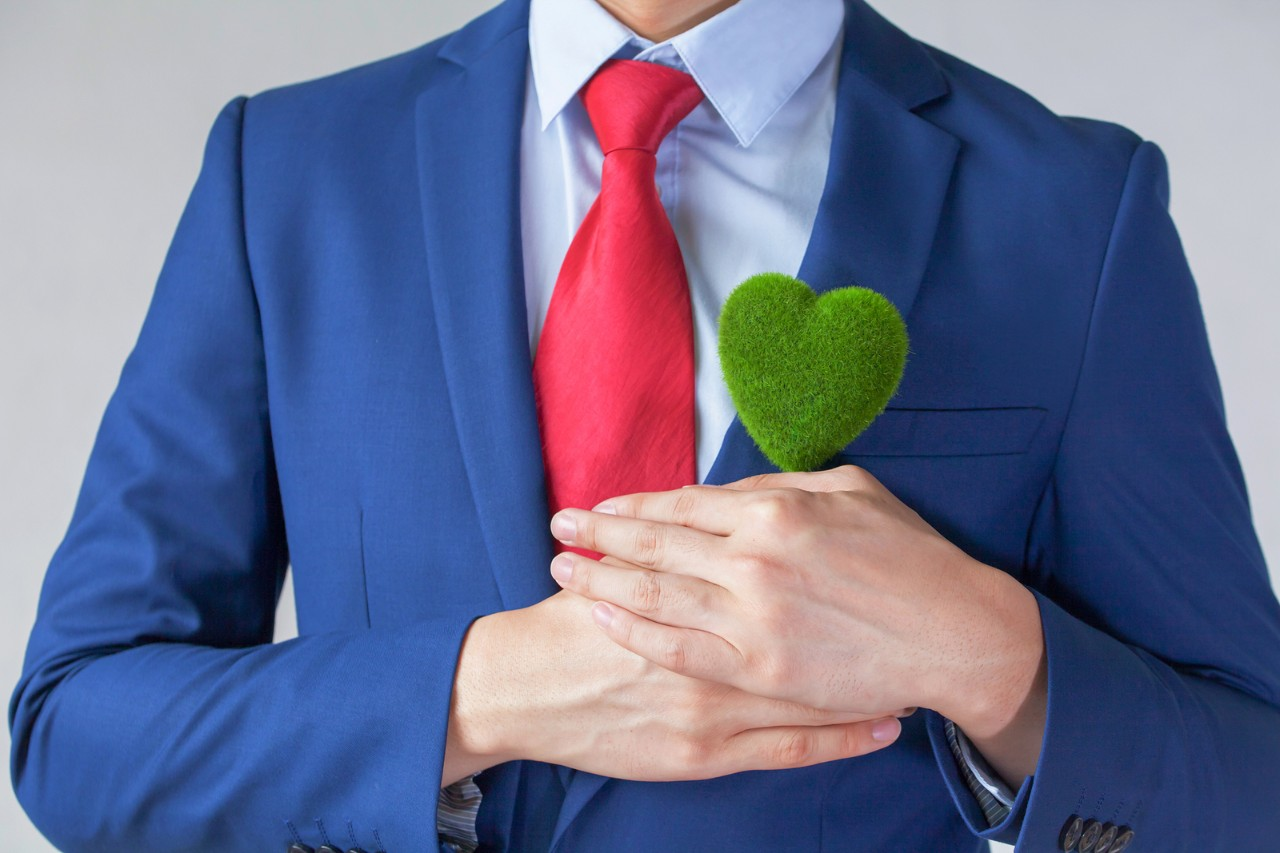 Businessman in suit holding a green heart shape - white background - indicates eco-friendly social and environmental responsibility business concept