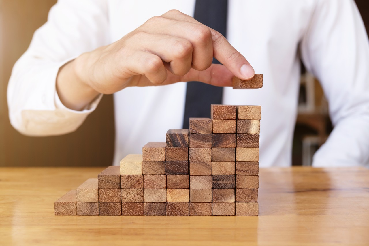 The way planning for business growth with wooden blocks, hand of business man is putting wooden block finally piece, plan and strategy in business.