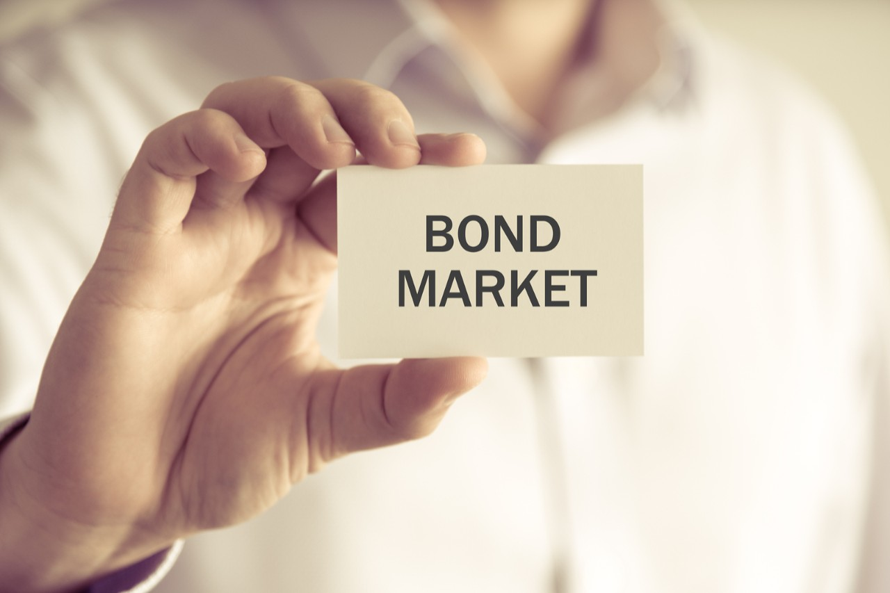 Closeup on businessman holding a card with text BOND MARKET business concept image with soft focus background and vintage tone